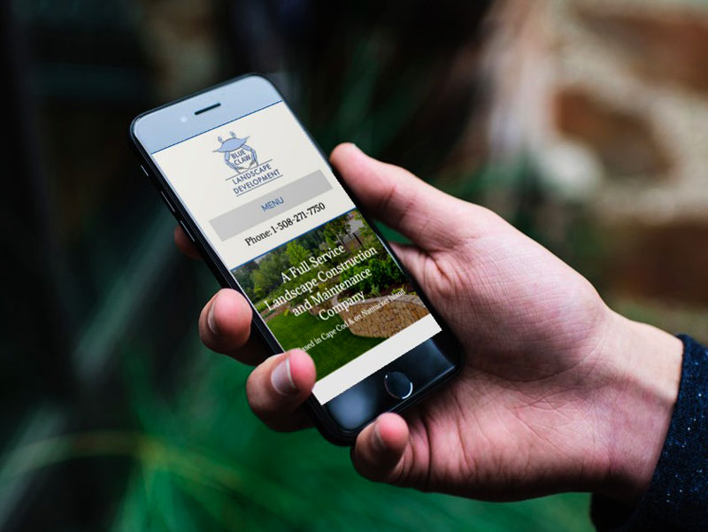 Photo of the Blue Claw Landscape Development and Maintenance Website on a Mobile Phone